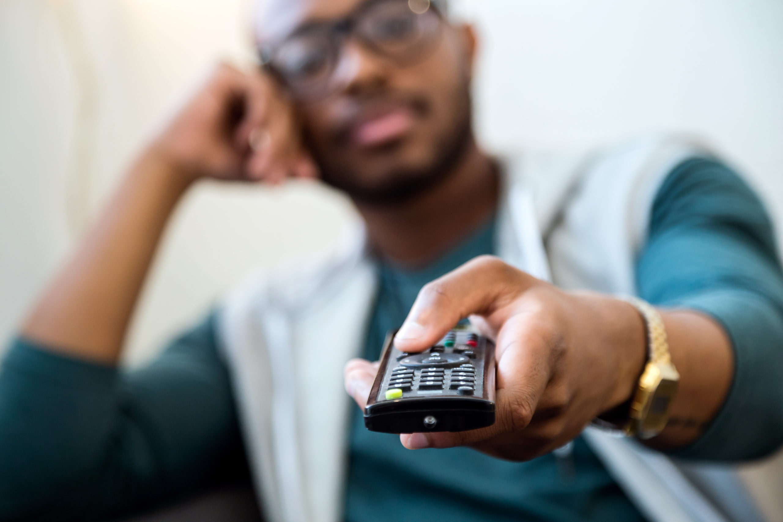 https://elements.envato.com/handsome-young-black-man-watching-tv-at-home-WBR2Y5S