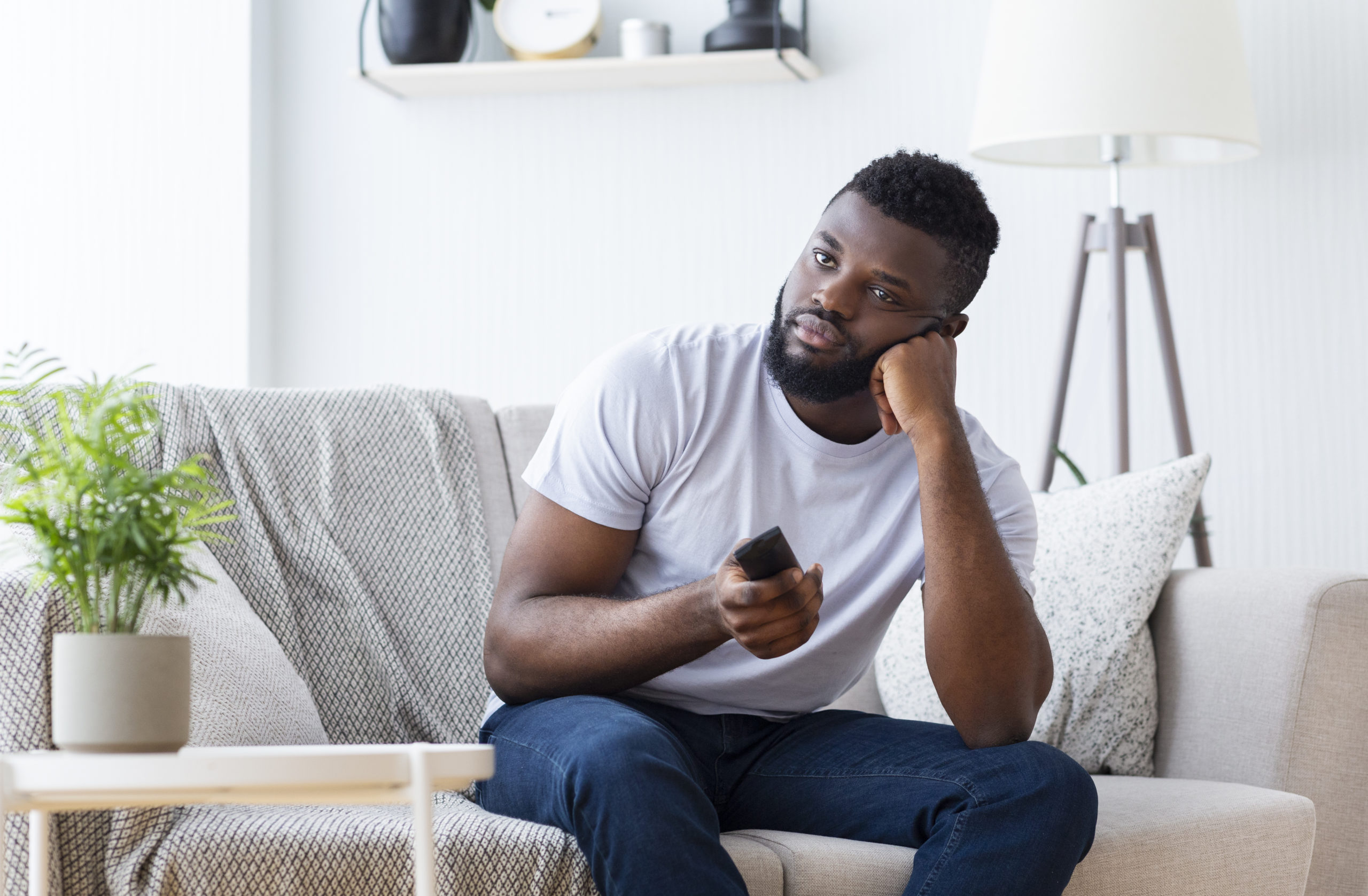 https://elements.envato.com/bored-african-guy-sitting-at-home-switching-tv-for-JDL625U