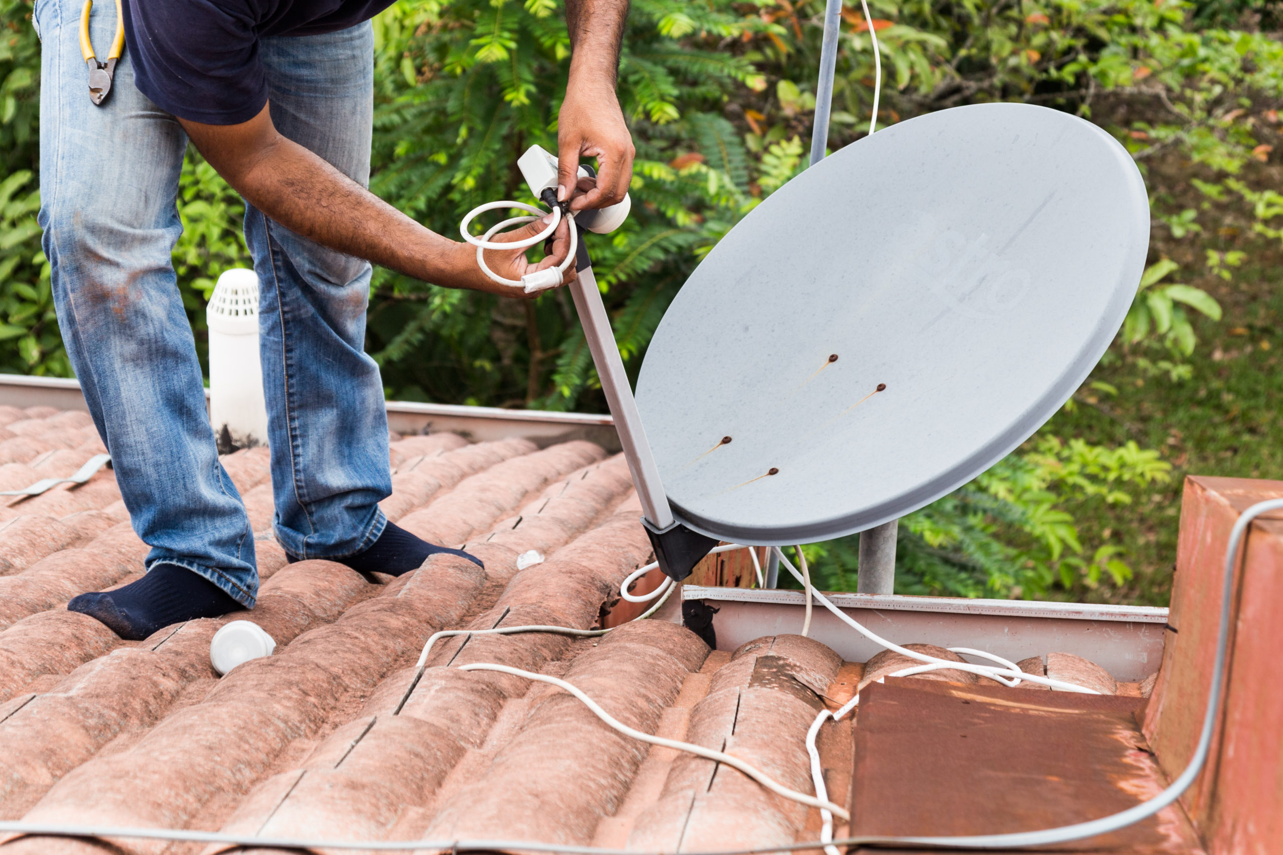 Worker installing satellite dish and antenna on roof top - https://elements.envato.com/worker-installing-satellite-dish-and-antenna - https://elements.envato.com/worker-installing-satellite-dish-and-antenna-on-ro-P64UPCM