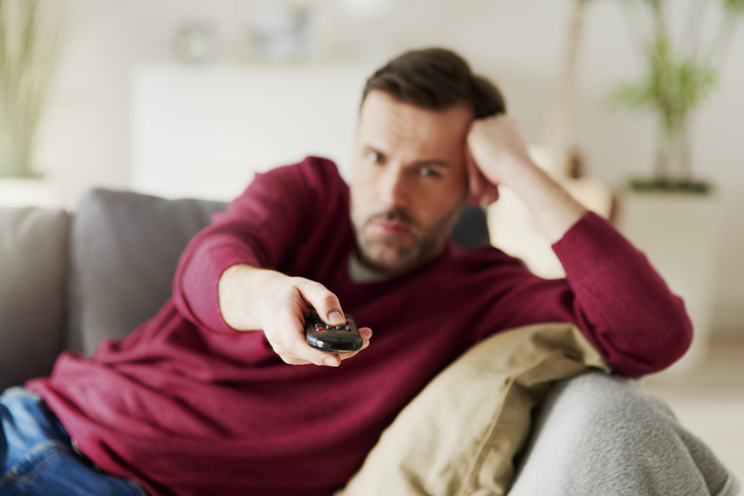 https://elements.envato.com/bored-man-holding-a-remote-and-watching-tv-XBTNVMD