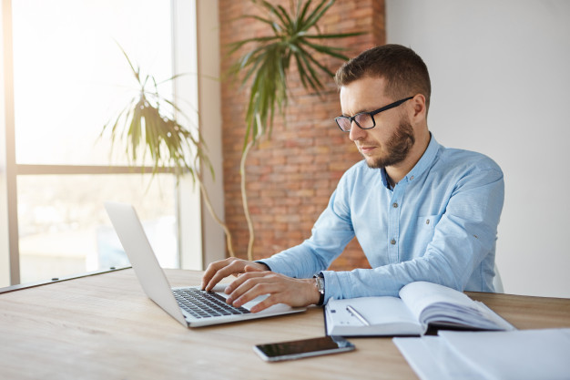 Man with glasses sitting down working on a laptop