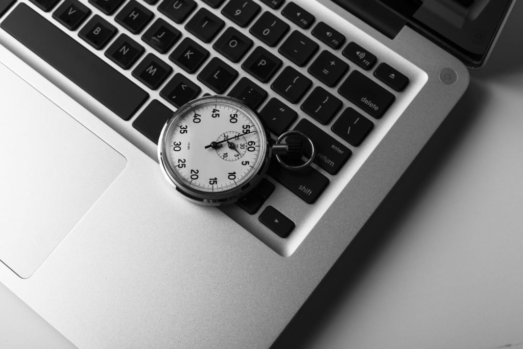 Silver laptop with stopwatch on the keyboard closeup