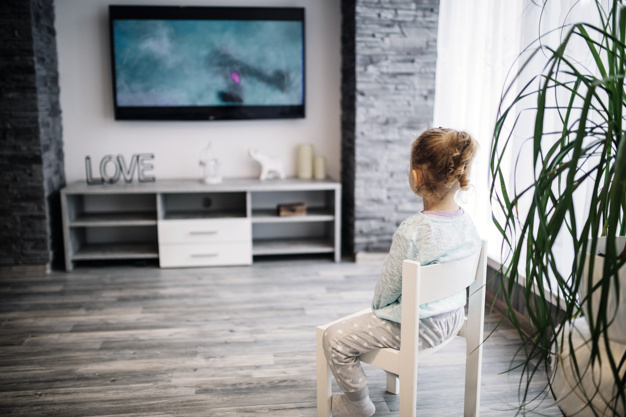 little girl sitting on a chair watching tv