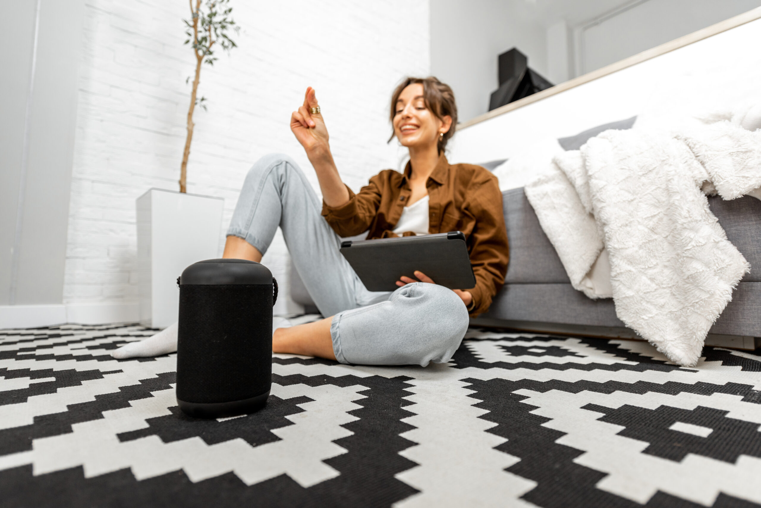 Woman with a smart speaker and tablet at home
