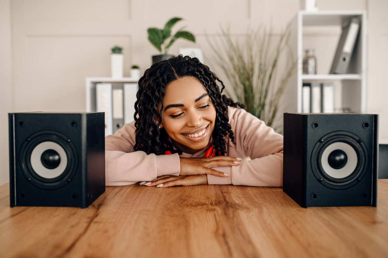 A woman smiling between two speakers - Denon Ceol N10 review