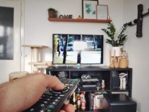 Hand on remote pointing at TV