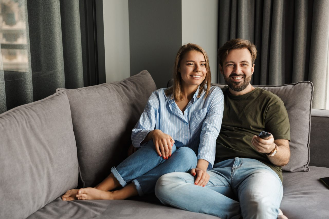 Couple watching TV using remote control - How to update humax freesat channels