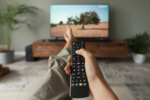Person pointing remote control at smart TV