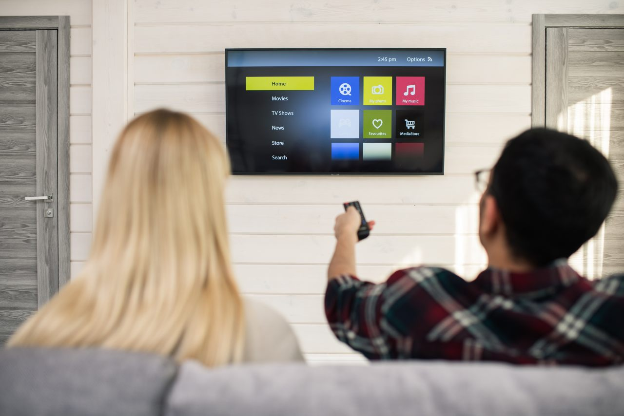 Best 40 inch smart tv - Man choosing what to watch on TV